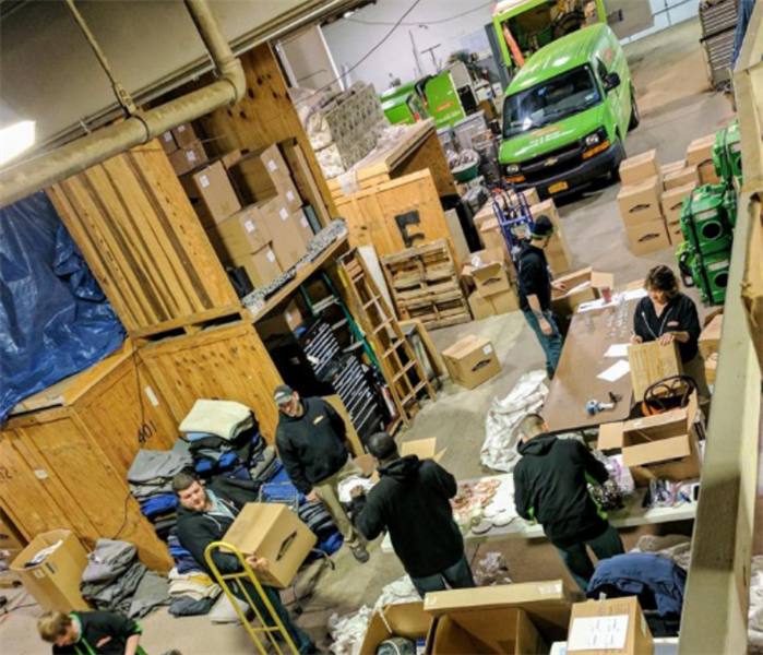 multiple people in warehouse sorting through boxex