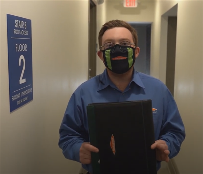 Dan from SERVPRO standing in a hallway with a padfolio.