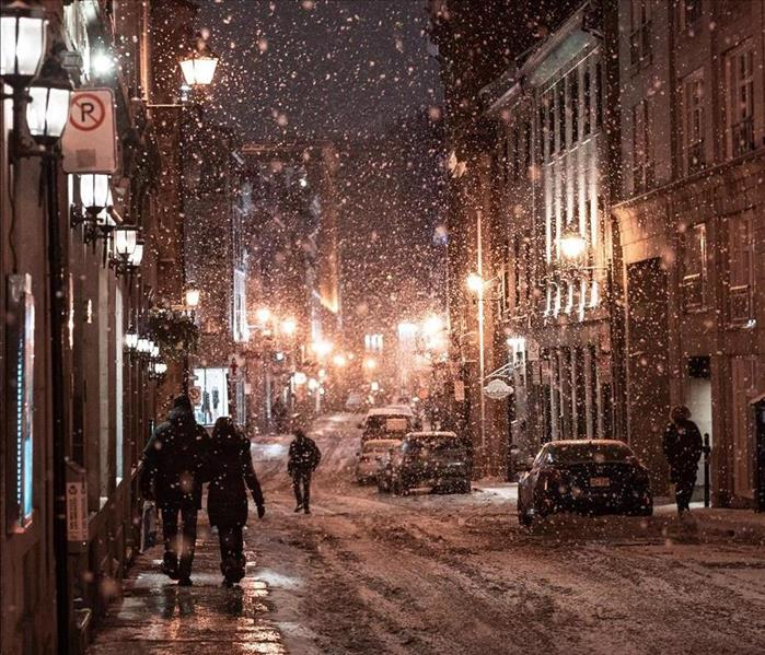 Two people with backs to the camera walk down a city sidewalk at night in a snowstorm.