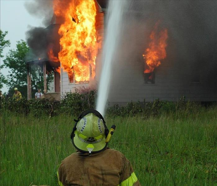 Firefighter in field with grass and flowers spraying hose on house on fire.
