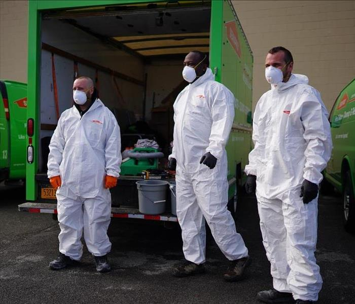 Three SERVPRO techs in Tyvek preparing to disinfect a building.
